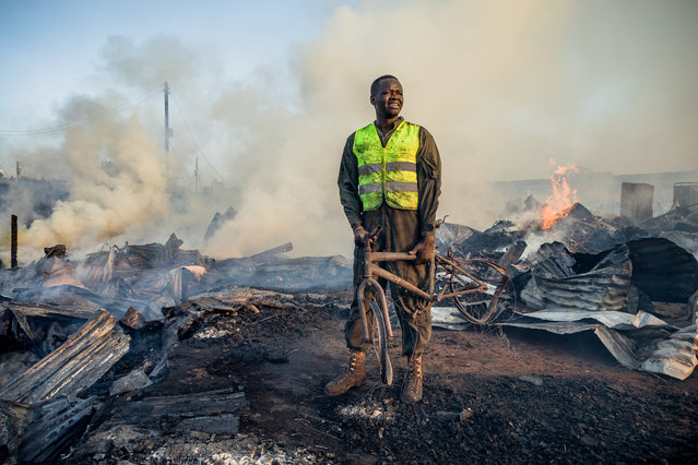 A resident who helps firefighters holds a burnt bicycle after a fire at Toi Market selling second hand clothes at Kibera slum in Nairobi, Kenya, on March 12, 2019. (Photo by Brian Otieno/AFP Photo)