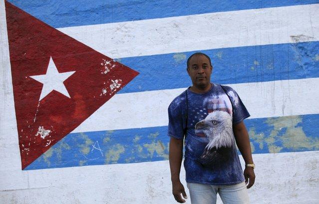 Miguel, 54, stands near a Cuban flag, while wearing a shirt with a U.S. flag design, in Havana March 8, 2016. (Photo by Enrique de la Osa/Reuters)