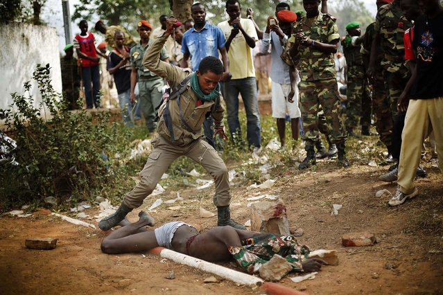A newly enlisted FACA (Central African Armed Forces) soldier stabs the lifeless body of a suspected Muslim Seleka militiaman moments after Central African Republic Interim President Catherine Samba-Panza addressed the troops in Bangui, Wednesday February 5, 2014. The victim was lynched by hundreds of recruits. (Photo by Jerome Delay/Associated Press)