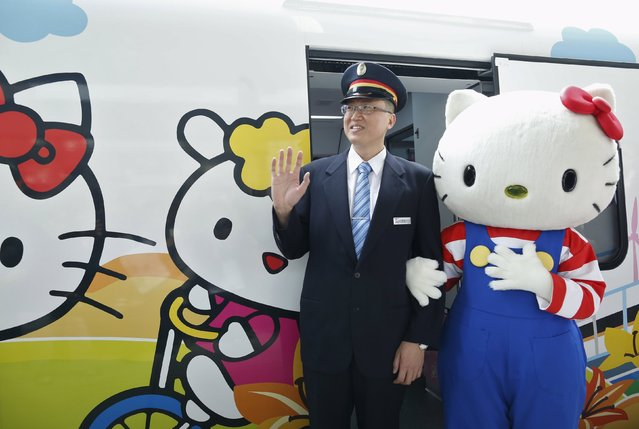 A performer dressed as Hello Kitty, poses with a conductor next to a Hello Kitty-themed Taroko Express train in Taipei, Taiwan March 21, 2016. (Photo by Tyrone Siu/Reuters)