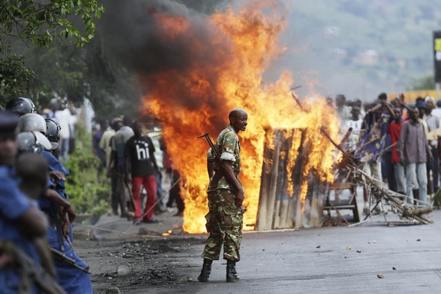 A soldier stands between demonstrators and riot police facing off in the Musaga district of  Bujumbura, Burundi, Monday May 4, 2015. Anti-government demonstrations resumed in Burundi's capital after a weekend pause as thousands continue to protest the president's decision to seek a third term. (Photo by Jerome Delay/AP Photo)