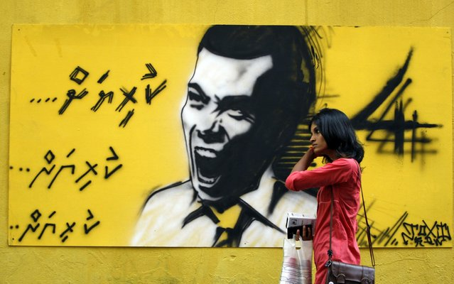 In this September 5, 2013, file photo, a woman walks past a graffiti of former President Mohamed Nasheed in Male, Maldives. Maldives has been in a political turmoil since last year's February resignation of Nasheed, who was elected in 2008 in the nation's first democratic polls after 30 years of autocracy. (Photo by Sinan Hussain/AP Photo)