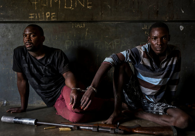 Two rhino poachers, one 19, the other 28 years old, apprehended by an anti-poaching team in Mozambique close to Kruger National Park border. They are seen waiting to be processed in the local jail. After a three-day chase, they were caught in a roadblock and the rifle seized shortly thereafter. This was due to a coordinated effort between Kruger National Park in South Africa where the poachers intended to shoot rhino for their horn; and Sabi Game Park, a conservancy on the Mozambique side. The poachers were tracked and identified by their unique shoe pattern. They tried to say they had been on their way to buy cattle, but had no money on their persons, and when asked the alleged cattle owner said he did not know anything about selling his cattle. A Czech CZ .458 hunting rifle was seized, complete with a professionally built silencer. Both men admitted their guilt and will be charged under new Mozambican law which states that possession of the weapon and bullets indicates intent to poach rhino. This carries a maximum sentence of 12 years and/or $80,000.00. Their Toyota Hilux vehicle was also confiscated. The younger of the two poachers later led police to the homes of suspected weapons and transport suppliers, higher-ups in the rhino poaching syndicates known as level 2's and 3's. Those men had fled by the time the police arrived, but significant information was discovered in the form of identity documents, both real and forged, as well as banking account information. (Photo by Brent Stirton/Getty Images for National Geographic Magazine/Courtesy of World Press Photo Foundation)