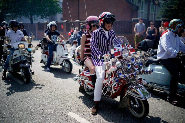 Scooter riders take part in the Manchester St George's Day parade on April 22, 2019 in Manchester, England. Various parades have taken place across the country, ahead of Sr George's Day tomorrow, to celebrate the patron saint of England. His emblem, a red cross on a white background is the flag of England. The cross of Saint George is incorporated in the Union Flag representing the United Kingdom. (Photo by Christopher Furlong/Getty Images)