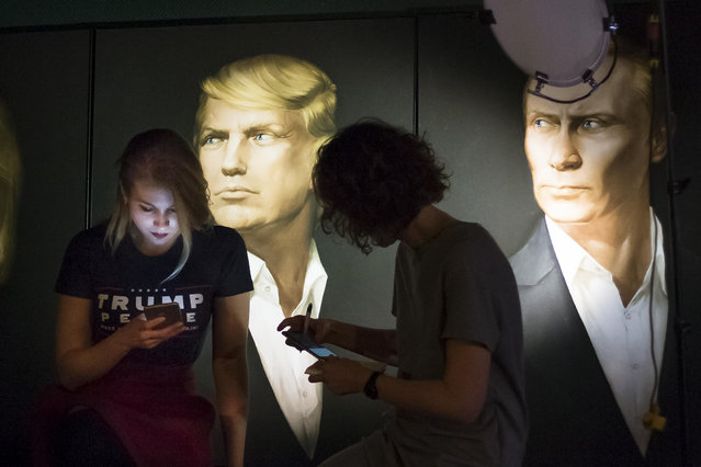 In this photo taken on Wednesday, November 9, 2016, Maria Katasonova, left, looks at her smart phone during a live telecast of the U.S. presidential election in the Union Jack pub, with pictures of Donald Trump and Russian President Vladimir Putin in the back, in Moscow, Russia. Maria Katasonova, a pro-Kremlin political activist, said many Russians shuddered at the prospect of a Clinton victory because they hold her responsible for the breakdown in ties as secretary of state in Obama's first term. (Photo by Alexander Zemlianichenko/AP Photo)