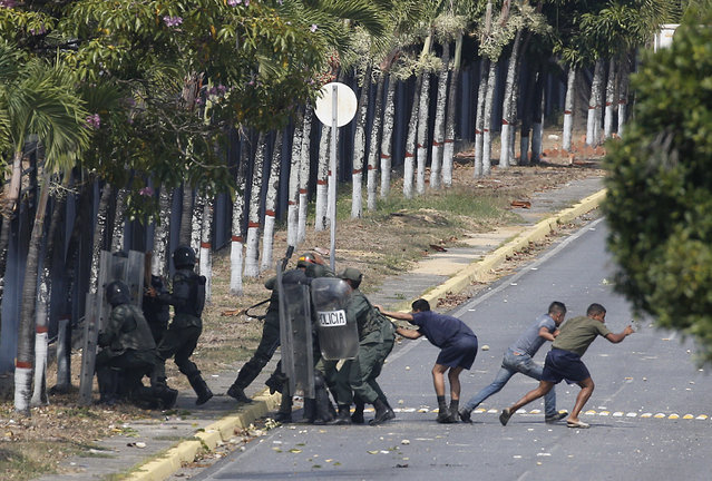 Security forces, some in civilian clothing, take positions inside La Carlota airbase during clashes with anti-government protesters in Caracas, Venezuela, Wednesday, May 1, 2019. (Photo by Ariana Cubillos/AP Photo)