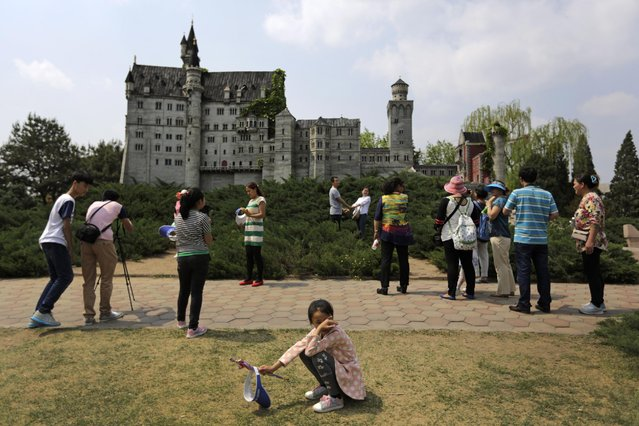 A child rests as visitors take souvenir photos near the replica of Germany's Neuschwanstein Castle at the World Park in Beijing, China, Saturday, May 2, 2015. Millions of Chinese are taking advantage of the May Day holidays to visit popular tourist sites. (Photo by Andy Wong/AP Photo)