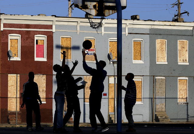 In this April 1, 2013 file photo, children play basketball at a park near blighted row houses in Baltimore. (Photo by Patrick Semansky/AP Photo)