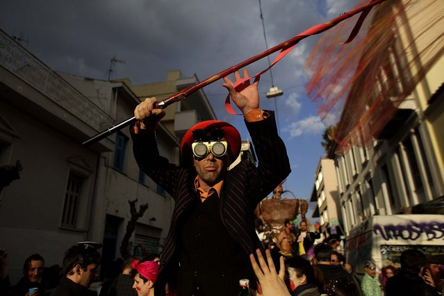 A costumed reveler takes part in an annual Carnival in Athens, Greece, February 23, 2014. (Photo by Kostas Tsironis/Associated Press)