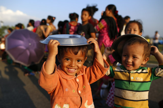 Nepalese earthquake survivor boys play with their plates as they line up during a food distribution in Kathmandu, Nepal, 13 May 2015. (Photo by Mast Irham/EPA)