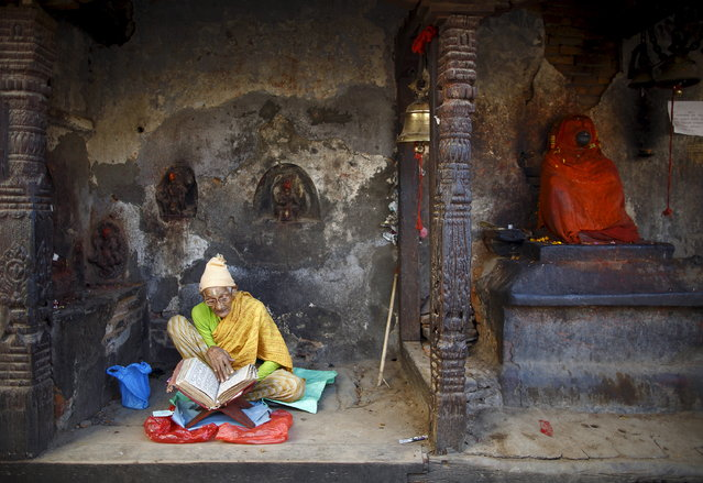 A woman offers prayers by reading a holy book as she sits in the remains of a temple after the earthquake in Kathmandu May 14, 2015. (Photo by Navesh Chitrakar/Reuters)