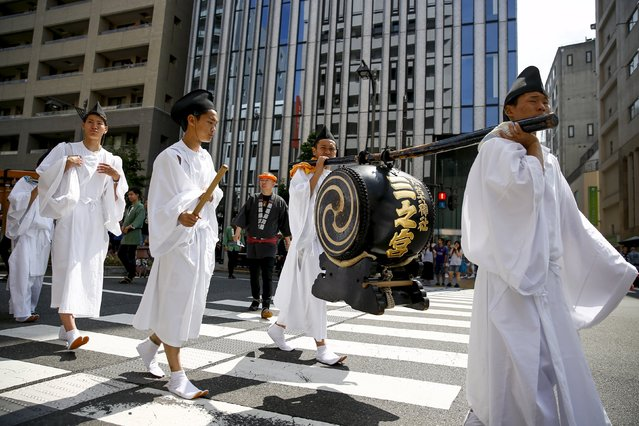 Men wearing Shinto robes lead a procession of portable shrines during the Sanja Matsuri festival in the Asakusa district of Tokyo May 17, 2015. (Photo by Thomas Peter/Reuters)