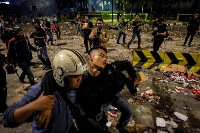 An injured police officer leaves the area with the help of his colleagues after clashes with protesters in Jakarta, Indonesia early May 23, 2019 in this photo taken by Antara Foto. (Photo by Rusyidi Zain/Antara Foto via Reuters)