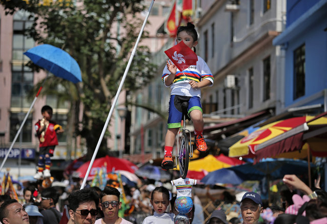 In this Sunday, May 12, 2019, file photo, a child dressed in a traditional Chinese costume floats in the air, supported by a rig of hidden metal rods, during a parade on the outlying Cheung Chau island in Hong Kong to celebrate the Bun Festival. Thousands of local residents and tourists flocked to an outlying island in Hong Kong to celebrate a local bun festival on Sunday. The festival features a parade with children dressed as deities floated on poles. (Photo by Vincent Yu/AP Photo/File)