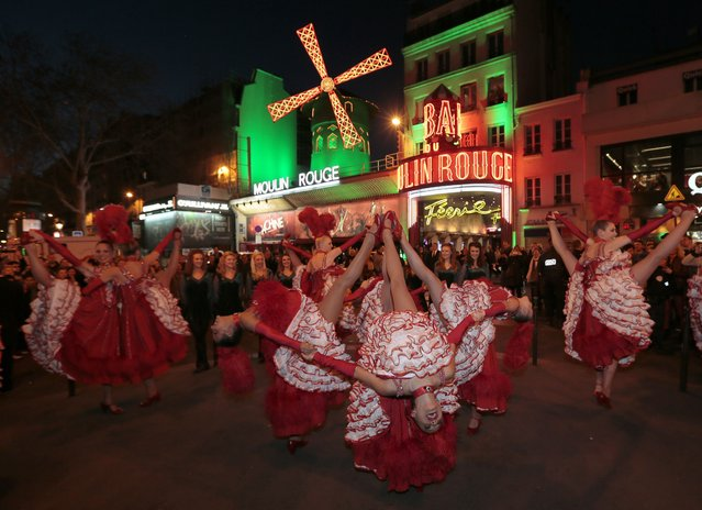Dancers perform in front of the Moulin Rouge cabaret in the Montmartre neighbourhood in Paris, on March 16, 2014, as it illuminated in green on the eve of Saint Patrick's day. (Photo by Jacques Demarthon/AFP Photo)