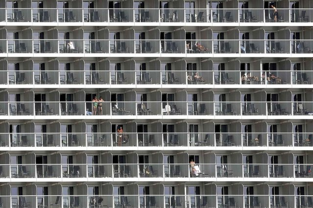 Vacationers are seen on cabin balconies of the 347-meter Quantum of the Seas cruise ship docked at the port of Piraeus near Athens, Monday, May 18, 2015. Greece's cash strapped government is examining ways to improve tax collection from the country's key tourism sector as it struggles to continue payments to bailout lenders. (Photo by Petros Giannakouris/AP Photo)
