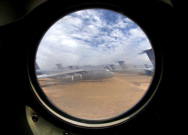 A field of Lockheed C-5 Galaxy cargo jets are seen through a window from another C-5 at the 309th Aerospace Maintenance and Regeneration Group boneyard at Davis-Monthan Air Force Base in Tucson, Ariz. on Thursday, May 21, 2015. The C-5A Galaxy is the largest aircraft in the U.S. armed services. The C-5 has a wingspan of over 222 feet and stands over 65 feet high has been used by the Air Force continually since 1969. (Photo by Matt York/AP Photo)