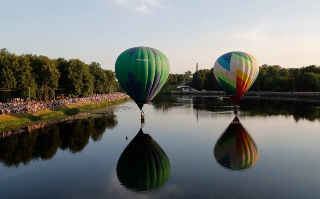 Hot air balloons fly over Lovat River during the 24th International Balloon Meet in Velikie Luki, Pskov region, Russia on June 11, 2019. (Photo by Anatoly Maltsev/EPA/EFE/Rex Features/Shutterstock)