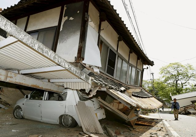 A man walks near a damaged house and car caused by an earthquake in Mashiki town, Kumamoto prefecture, southern Japan, in this photo taken by Kyodo April 15, 2016. (Photo by Reuters/Kyodo News)