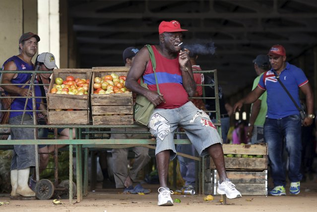 A man selling tomatoes smokes at a wholesale market in Havana April 13, 2016. (Photo by Enrique de la Osa/Reuters)