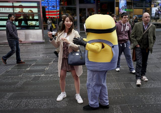A man dresses as a Minion tries to convince a tourist to have her picture taken with him, in Times Square, in New York, April 7, 2016. The assortment of costumed characters, painted naked women and ticket sellers who make the streets of New York's Times Square their office, catering to tourists, may soon be restricted after a City Council vote Thursday. (Photo by Rickey Rogers/Reuters)