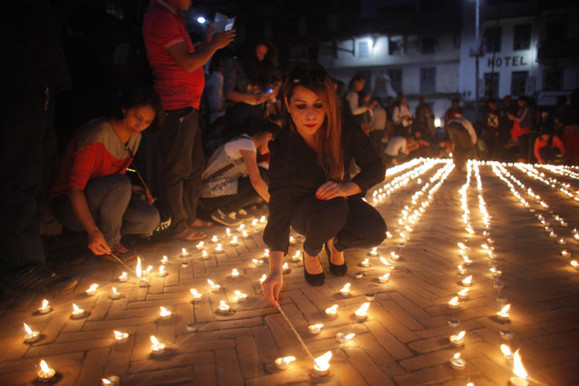 Nepalese people light candles in memory of those who died in last year's devastating earthquake in Basantapur Durbar Square in Kathmandu, Nepal, Sunday, April 24, 2016. Nepalese held memorial services to mark the anniversary of the disaster that killed nearly 9,000 people and left millions homeless. (Photo by Niranjan Shrestha/AP Photo)