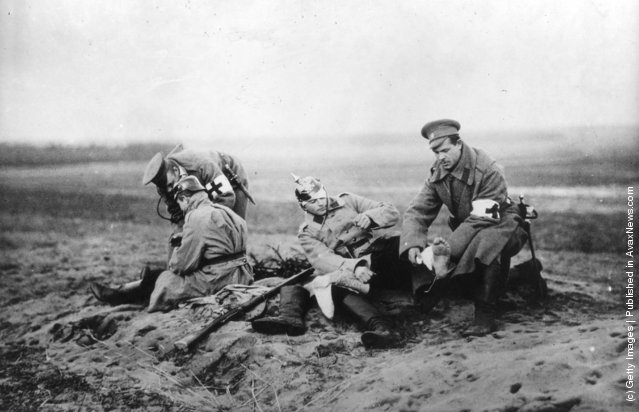 1915:  Red Cross personnel attending to wounded soldiers on a Russian battlefield during the First World War