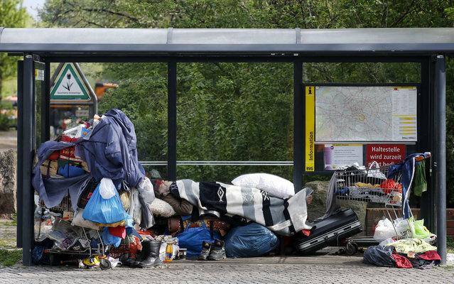 A homeless man sleeps amongst his possessions inside a bus stop at Berlin's Kreuzberg district, April 8, 2014. (Photo by Fabrizio Bensch/Reuters)