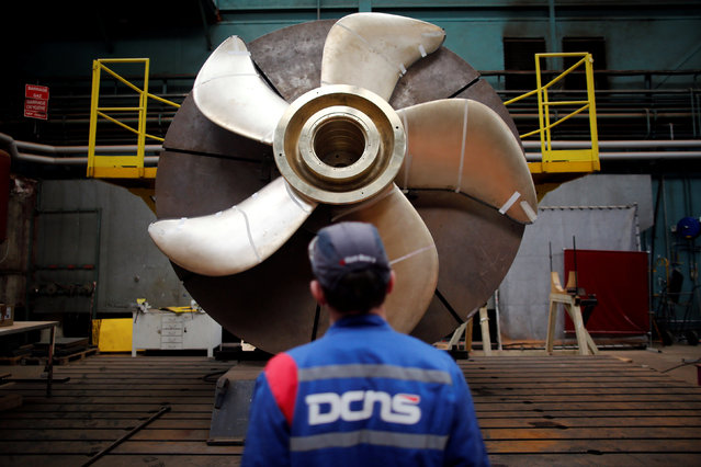 An employee looks at the propeller of a Scorpen submarine at the industrial site of the naval defence company and shipbuilder DCNS in La Montagne near Nantes, France, April 26, 2016. (Photo by Stephane Mahe/Reuters)