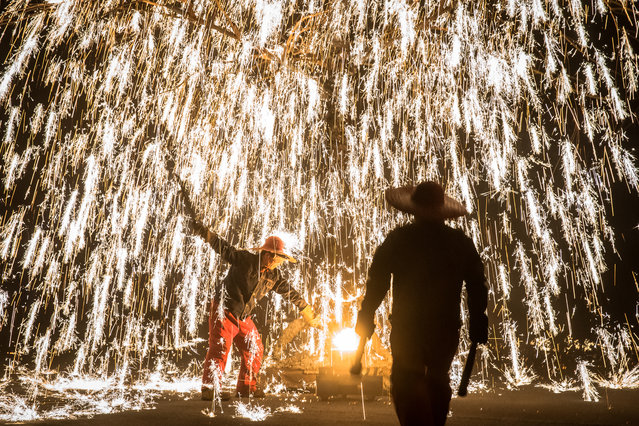 """Artists perform with molten metal to create sparks like fireworks during the """"Molten Metal Sparks (Datiehua)"""" show, near Badaling Great Wall, in Yanqing district of Beijing, China, 07 February 2019. """"Datiehua"""" is an ancient Chinese firework show where artists perform in different ways with molten metal to create sparks like fireworks. When metal is melted down it has a temperature of 1600 degrees Celsius. Its typical shows include Jing Tao Hai Lang (raging waves), Huo Shu Jin Hua (fiery trees and gold flowers), Er Long Xi Zhu (two dragons playing with a pearl), Kong Zhong Li Huo (thunderbolt) and other. The performance has become popular in recent years and thousands of people watch it every day during the Spring Festival period. The Chinese Lunar New Year, the Year of the Pig, began on 05 February 2019. (Photo by Roman Pilipey/EPA/EFE)"""