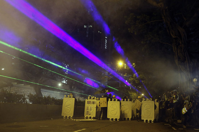 Protesters huddle behind barriers and use laser beams to shine at riot police during confrontation in Tsim Sha Tsui in Hong Kong on Saturday, August 3, 2019. Hong Kong protesters ignored police warnings and streamed past the designated endpoint for a rally Saturday in the latest of a series of demonstrations targeting the government of the semi-autonomous Chinese territory. (Photo by Steve Leung/HK01 via AP Photo)