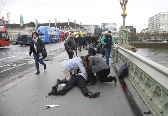 Injured people are assisted after an incident on Westminster Bridge in London, Britain on Wednesday, March 22, 2017. (Photo by Toby Melville/Reuters)