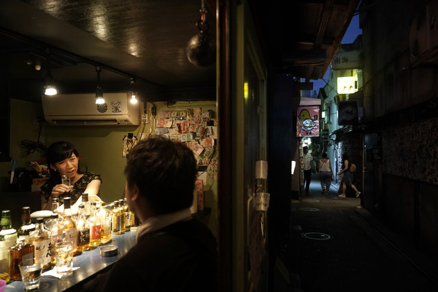 Bar owner Marie Yoshida, far left, chats with a patron in her bar at the Golden Gai in the Shinjuku district of Tokyo, July 28, 2019. (Photo by Jae C. Hong/AP Photo)