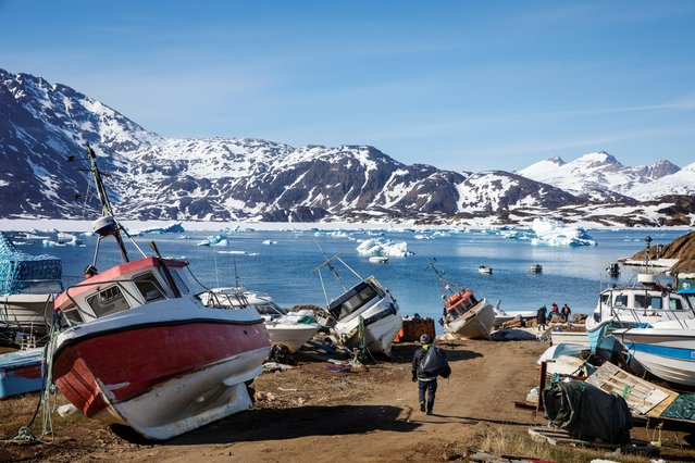 A man walks to his boat past a number of abandoned and dry-docked boats in the town of Tasiilaq, Greenland, June 15, 2018. (Photo by Lucas Jackson/Reuters)