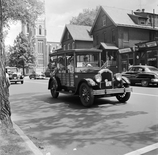A 1925 Buick station wagon which used real wood for the frame driving through a small town during the 50th Anniversary of the Hartford Automobile Club, United States. Circa 1955. (Photo by Three Lions/Getty Images)