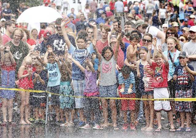 Children cheer as they get sprayed by water during the Firefighter Muster event at the World Fire and Police Games in Fairfax, Virginia July 4, 2015. (Photo by Jonathan Ernst/Reuters)