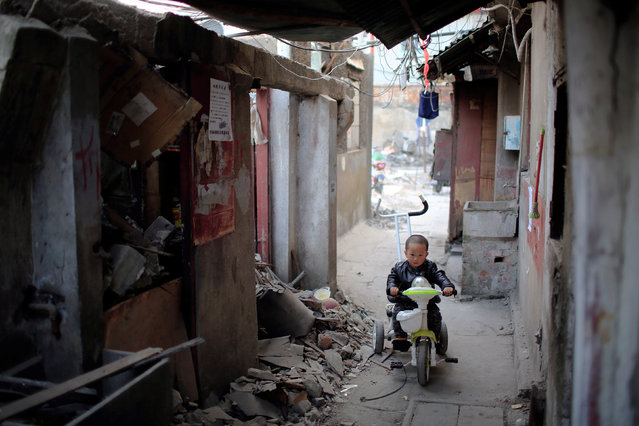 A boy rides a tricycle in between semi demolished houses in Guangfuli neighbourhood, in Shanghai, China, March 28, 2016. (Photo by Aly Song/Reuters)