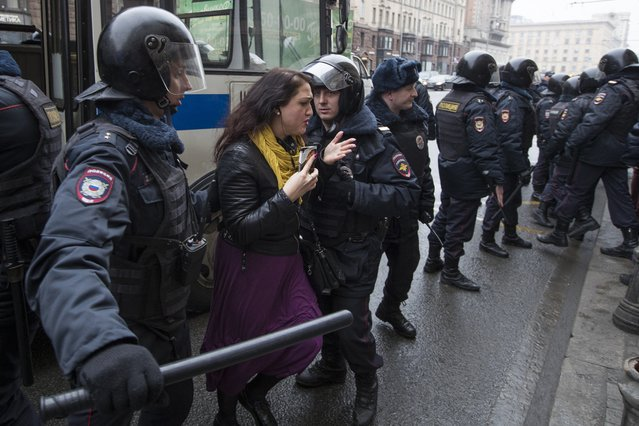 Police officers try to detain a woman in the main street in Moscow, Russia, Sunday, April 2, 2017. (Photo by Pavel Golovkin/AP Photo)