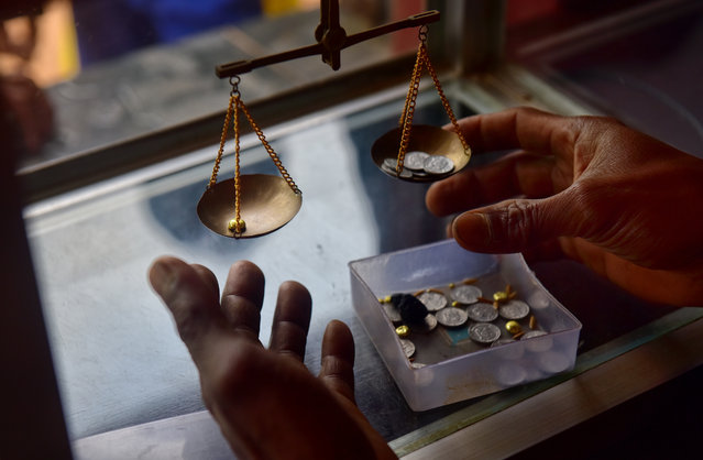 A local buyer weighing gold that was brought in by small scale miners on March 22, 2017 in Paracale, Philippines. (Photo by Jes Aznar/Getty Images)