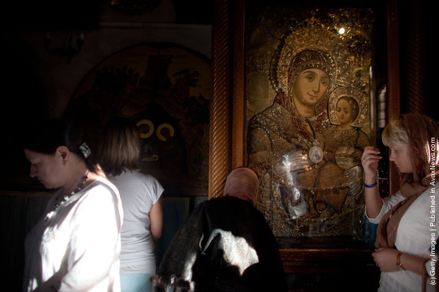 Women pray in the Church of the Nativity
