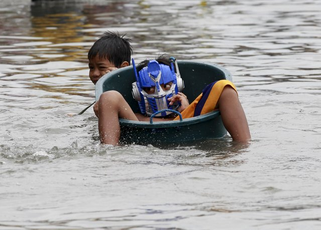 A boy tugs on a water basin with his friend wearing a mask as he wades through deep flooding caused by typhoon Linfa, locally named Egay, at Longos town in Malabon City, north of Manila July 6, 2015. (Photo by Romeo Ranoco/Reuters)