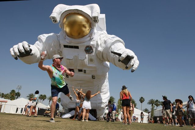 A man poses for friends in front of the giant moving inflated astronaut art piece, Escape Velocity, at the Coachella Valley Music & Arts Festival at the Empire Polo Club in Indio, California, April 12, 2014. The annual music festival, which runs for two consecutive three-day weekends, has grown to one of the largest music festival in the U.S. since it was founded in 1999. (Photo by David McNew/AFP Photo)