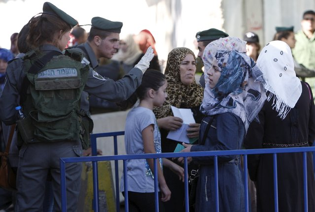 Palestinians wait to show their identity cards to Israeli security officers as they make their way to attend the fourth Friday prayer of Ramadan in Jerusalem's al-Aqsa mosque, at an Israeli checkpoint in the West bank city of Bethlehem July 10, 2015. (Photo by Mussa Qawasma/Reuters)
