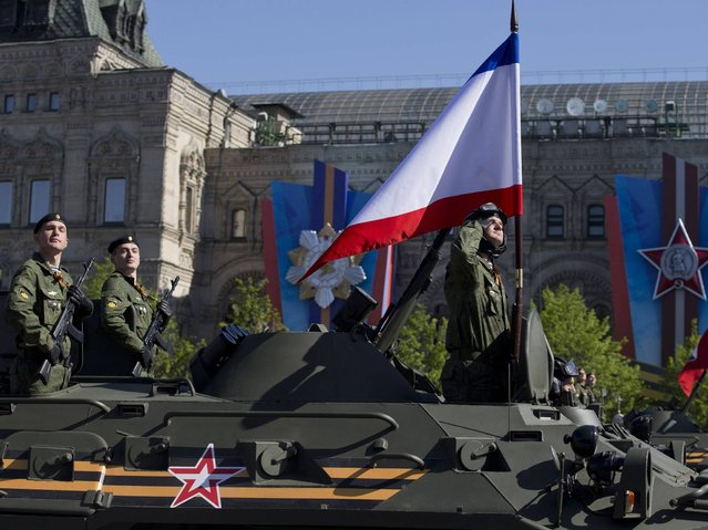 Russian troops ride an APC with a Crimean flag during the Victory Day Parade in Moscow. (Photo by Pavel Golovkin/AP Photo)