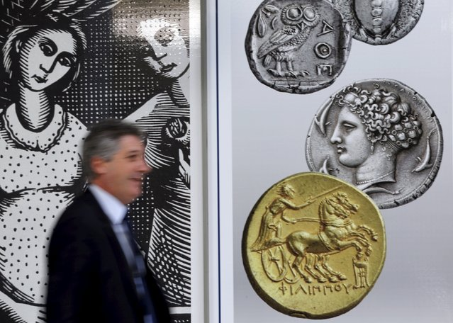 A man walks past pictures of ancient coins in central Athens, Greece, July 13, 2015. Euro zone leaders agreed on a roadmap to a possible third bailout for near-bankrupt Greece on Monday, but Athens must enact key reforms this week before they will start talks on a financial rescue to keep it in the European currency area. (Photo by Jean-Paul Pelissier/Reuters)