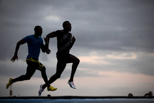 "Jamaican Olympic gold medalist Usain Bolt, right, runs with Antigua and Barbuda sprinter Daniel Bailey during a training session of the ""Mano a Mano"" challenge at Copacabana beach in Rio de Janeiro, Brazil, Friday, March 29, 2013. Bolt will compete, Sunday, on a track specially built at the famous beach, challenging Bailey, Ecuador's Alex Quinones, and a Brazilian athlete from a local qualifier. (Photo by Felipe Dana/AP Photo)"