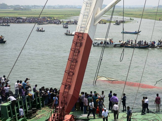 Bangladeshi rescuers work to raise a capsized ferry which sank during bad weather on the Meghna river in Munshiganj district. (Photo by Munir Uz Zaman/AFP Photo)