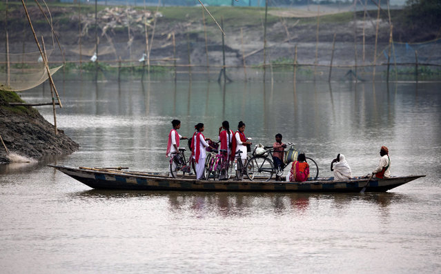 School children ride on a boat with their bicycles to cross the river Brahmaputra in Kasoshila village on the outskirts of Gauhati, India, Monday, October 21, 2019. Brahmaputra is one of Asia's largest rivers, which passes through China's Tibet region, India and Bangladesh before converging into the Bay of Bengal. (Photo by Anupam Nath/AP Photo)