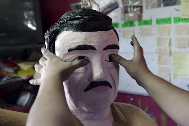 "A worker attaches eyes to a pinata depicting the drug lord Joaquin ""El Chapo"" Guzman at a workshop in Reynosa, July 21, 2015. Guzman broke out of Mexico's top maximum security prison through a tunnel built into his cell earlier this month. (Photo by Daniel Becerril/Reuters)"