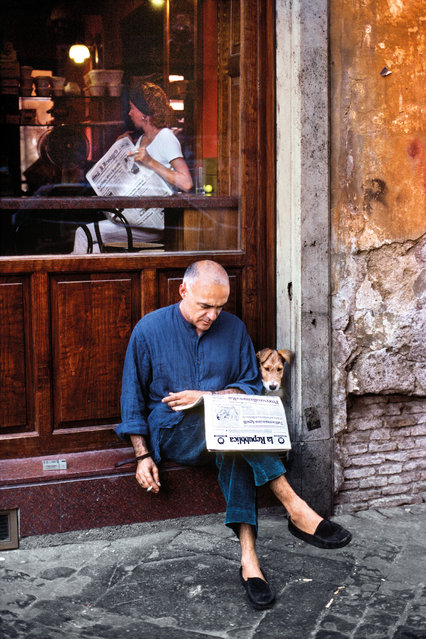 A man reads a newspaper with a dog. Rome, Italy, 1994. (Photo by Steve McCurry/The Guardian)